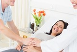 Happy pregnant woman with man and doctor