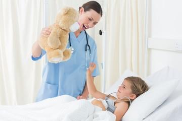 Doctor entertaining sick girl with teddy bear