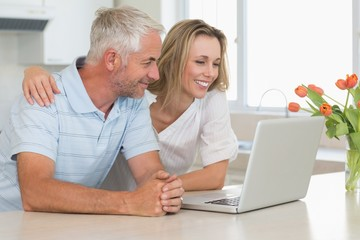Cheerful couple using laptop together at the worktop