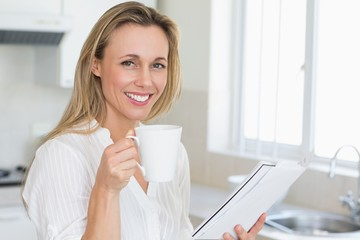 Smiling woman holding mug and newspaper