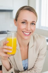 Happy businesswoman having orange juice before work in the