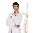 Thoughtful female doctor with skeleton model