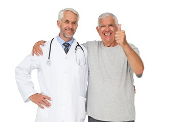 Portrait of a doctor with senior man gesturing thumbs up