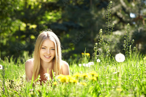 canvas print picture Spring girl lying on the field of dandelions