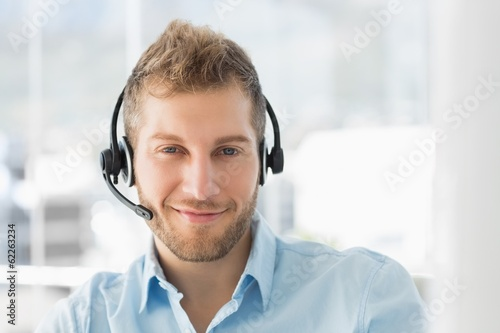 Handsome call centre agent wearing a headset