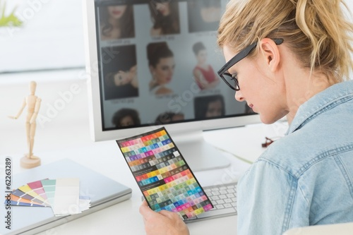 Blonde designer looking at colour chart at her desk
