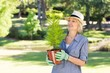 Woman looking at potted plant in garden