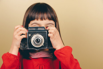 Little retro photographer with an old camera