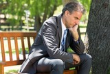 Depressed businessman sitting on park bench