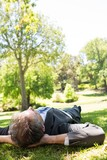 Businessman lying in park