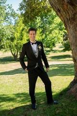 Handsome groom standing in garden