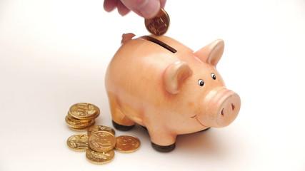 HD - Man throws a Coin in a Piggy Bank