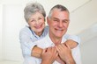 Affectionate retired couple smiling at camera