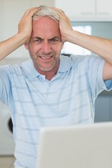 Stressed man using his laptop looking at camera