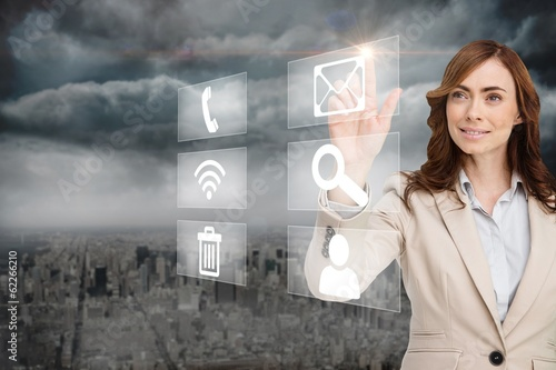 Smiling businesswoman pointing to email on app menu