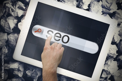 Hand touching seo on search bar on tablet screen