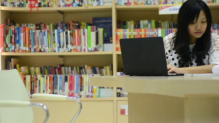 Asian student woman Using Laptop and typing book at library