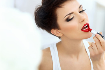 Beautiful Brunette applies lipstick. Red lips. Make up