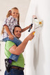 Happy father and little girl painting the room together
