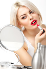 Woman applies red lipstick Red Lips and Blond Hair. Daily Makeup
