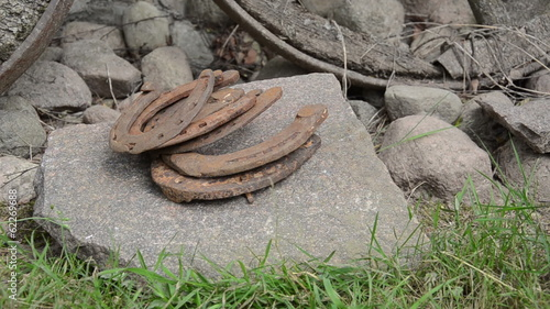 Closeup hand lay stack of retro rusty horse shoes on big stone