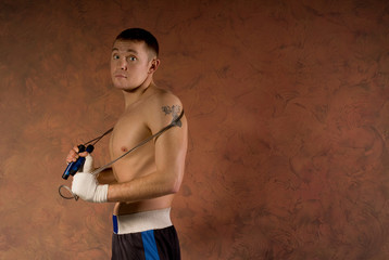 Young boxer in the gym with a skipping rope