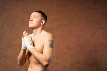 Young boxer praying before a match