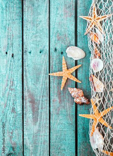 rozgwiazdy-i-muszle-w-sieci-rybackiej-na-starym-drewnianym-tle