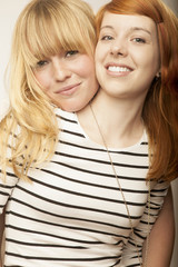 red and blond haired girls friends laughing and hug