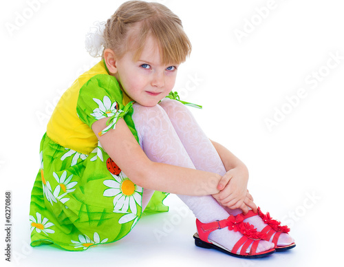 little girl sitting hugging her knees and smiling cheerfully.