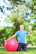 Man sitting in park with pilates ball