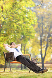 Relaxed businessman sitting on a bench in park