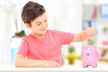 Boy inserting coins into a piggybank
