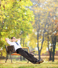 Businessman relaxing in park, seated on a wooden bench