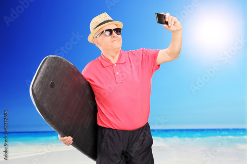 Mature surfer taking a selfie with cell phone