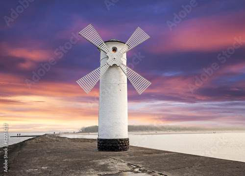 Lighthouse windmill with dramatic sunset sky, Swinoujscie, Balti