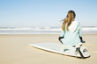 Teenage surfer girl sitting in the beach and checking the waves