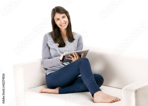 Beautiful woman sitting on the soda and working with a tablet