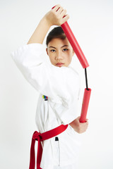 young taekwondo girl pose with nunchaku