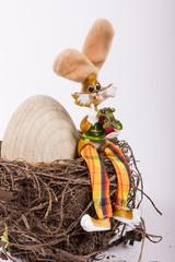 auf einem Nest sitzender Osterhase mit großem Holzei