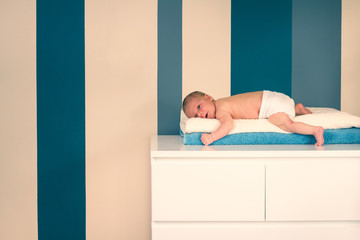 Newborn lying on a white commode