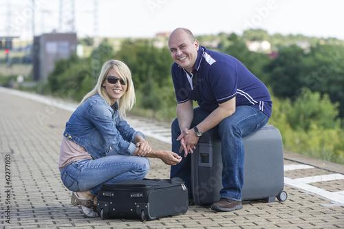 canvas print picture Paar mit Koffern am Bahnsteig
