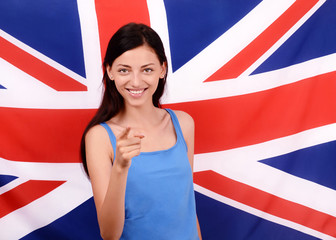 British girl smiling pointing in front to you.UK flag background