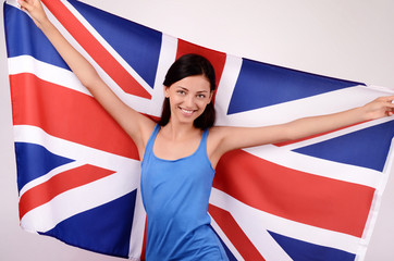 Beautiful British girl smiling holding up the UK flag.