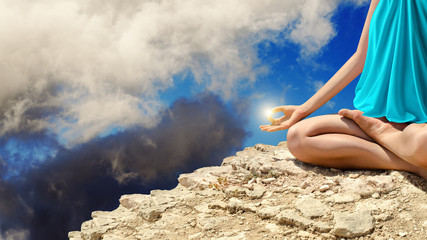 Young woman meditating on the rocks
