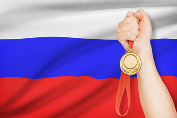 Medal in hand with flag on background - Russian Federation
