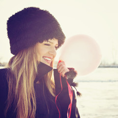 Cute teenage girl holding red balloon wearing black fur hat