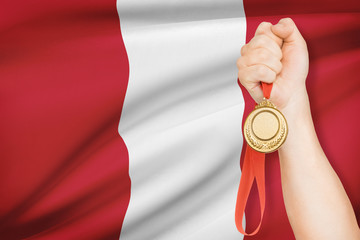 Medal in hand with flag on background - Republic of Peru