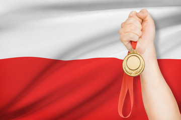 Medal in hand with flag on background - Republic of Poland