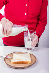 Seniorin schüttet Milch in ein Glas